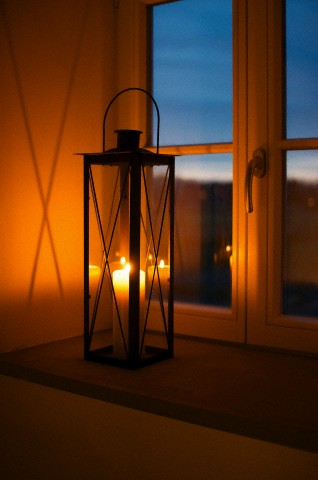 Lantern with lighted candle on window sill at dusk